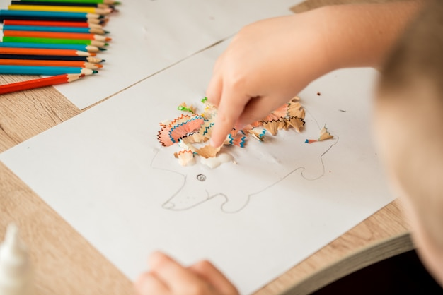 Menina bonitinha fazer apliques colas casa colorida, aplicando papel de cor usando cola ao fazer artes e ofícios na pré-escola ou em casa. idéia para a criatividade das crianças, um projeto de arte feito de papel.