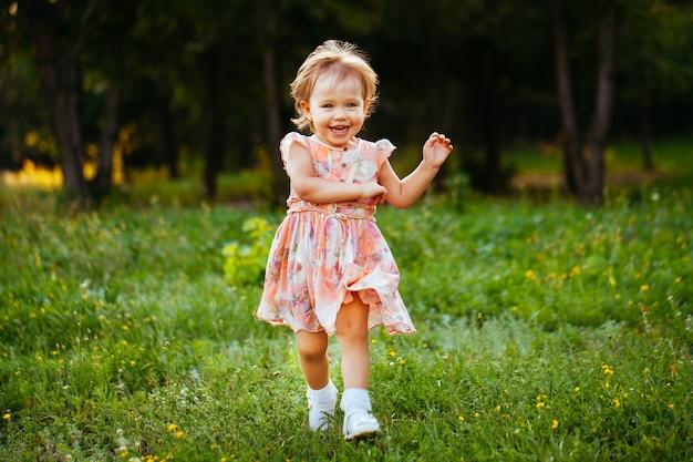 Menina bonitinha feliz correndo na grama do parque. felicidade.