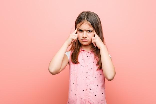 Menina bonitinha focada em uma tarefa, mantendo-o dedos apontando a cabeça.