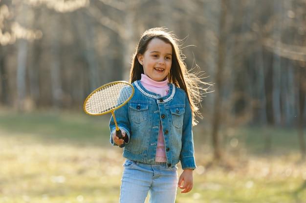 Menina bonitinha jogando badminton ao ar livre em dia de verão quente e ensolarado