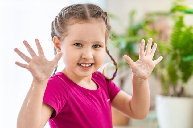 Menina bonitinha lava as mãos. a criança mostra palmas ensaboadas no quadro.