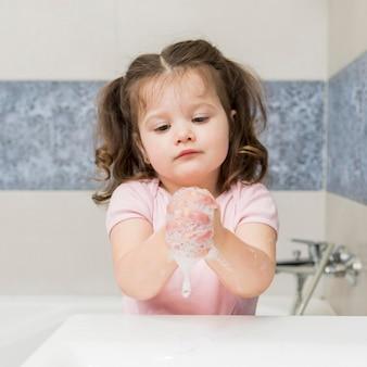 Menina bonitinha lavando as mãos