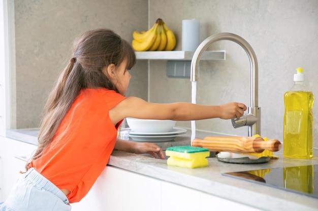 Menina bonitinha lavando prato na cozinha sozinha. criança alcançando a torneira da pia da cozinha e abrindo a água.