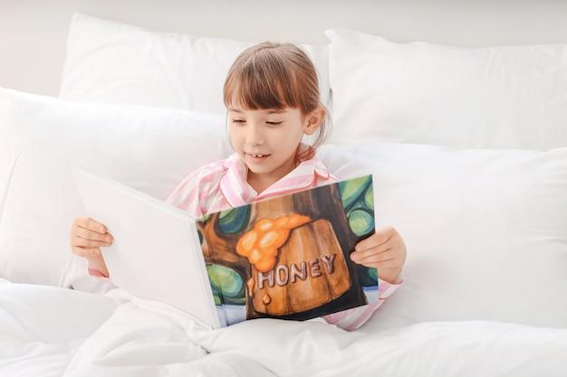Menina bonitinha lendo história para dormir em casa