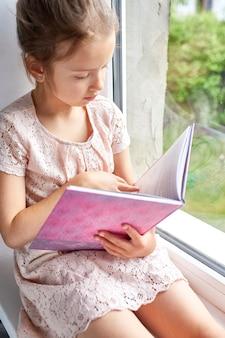 Menina bonitinha lendo livro em casa, no parapeito da janela