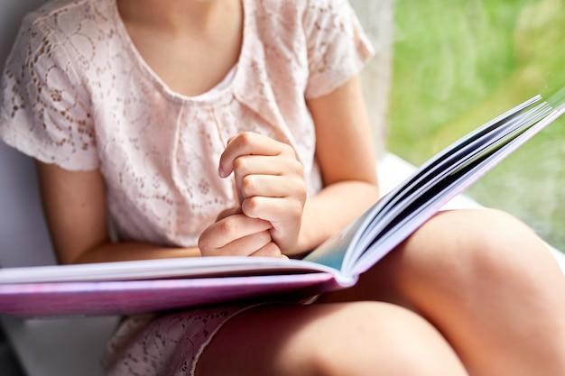 Menina bonitinha lendo livro em casa, no peitoril da janela, criança estudando em casa, quarentena, ficar em casa, estilo de vida.