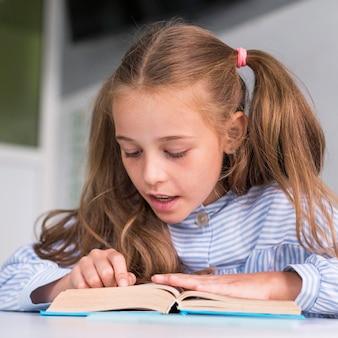 Menina bonitinha lendo na aula
