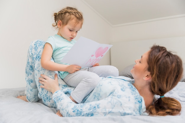 Menina bonitinha lendo o cartão enquanto está sentado no estômago da mãe em casa