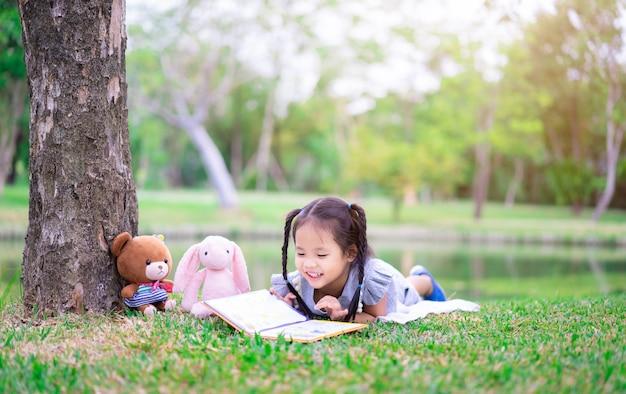 Menina bonitinha lendo um livro enquanto estava deitado com uma boneca no parque