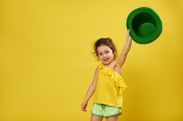 Menina bonitinha levanta a mão segurando um chapéu irlandês de duende verde.