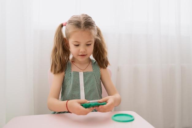 Menina bonitinha moldes de plasticina na mesa