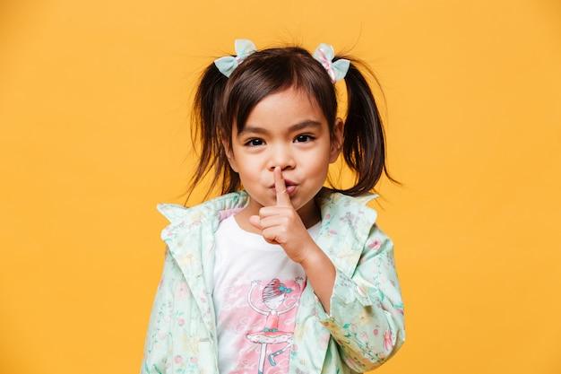 Menina bonitinha mostrando o gesto de silêncio.
