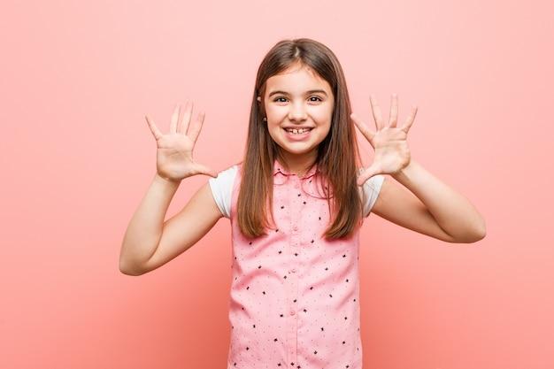 Menina bonitinha mostrando o número dez com as mãos.