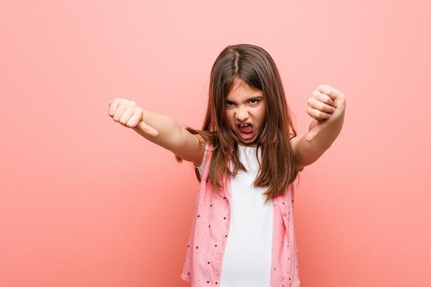 Menina bonitinha mostrando o polegar para baixo e expressando antipatia.