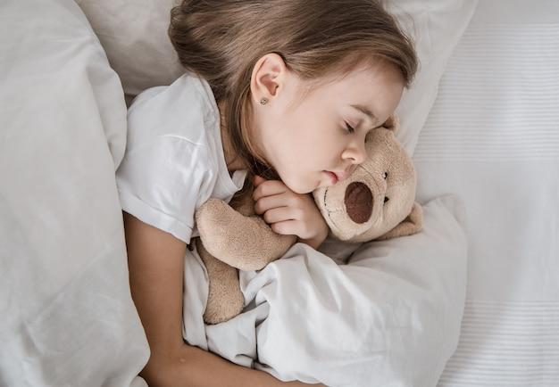 Menina bonitinha na cama com um brinquedo macio