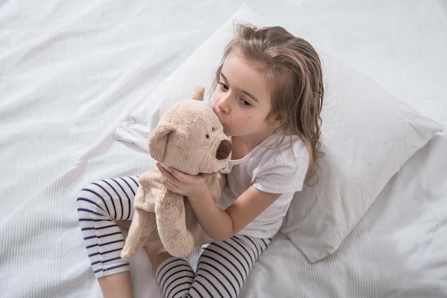 Menina bonitinha na cama com um brinquedo macio.