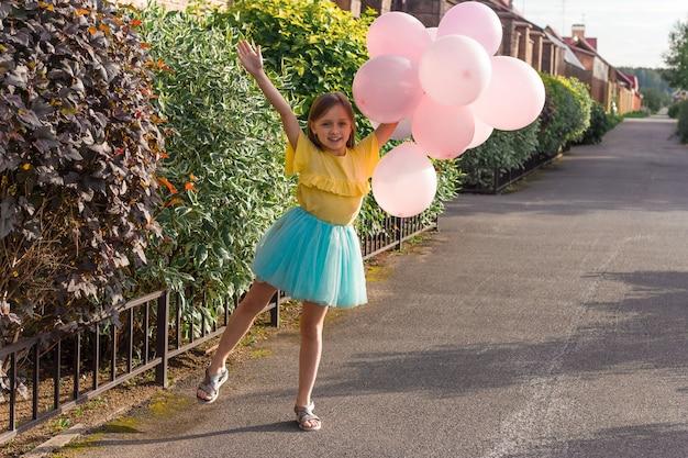 Menina bonitinha na camisa amarela e saia azul sorrindo e segurando um monte de balões