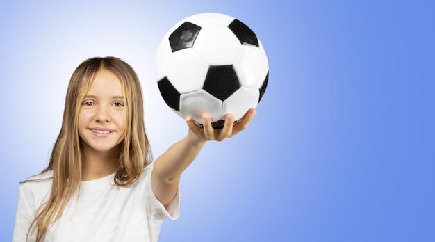 Menina bonitinha na camisa branca, segurando uma bola de futebol nas mãos