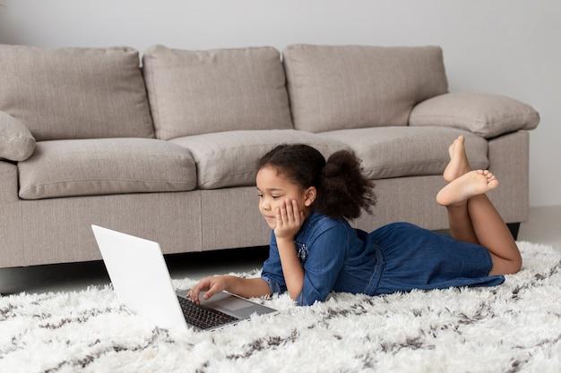 Menina bonitinha navegando laptop de casa