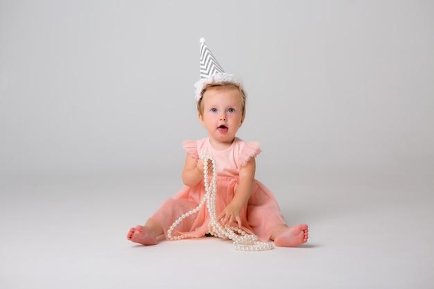 Menina bonitinha no boné de aniversário na luz