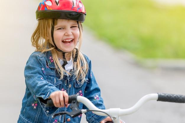 Menina bonitinha no capacete e jaqueta jeans em uma bicicleta
