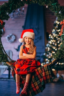 Menina bonitinha no chapéu de papai noel e vestido vermelho