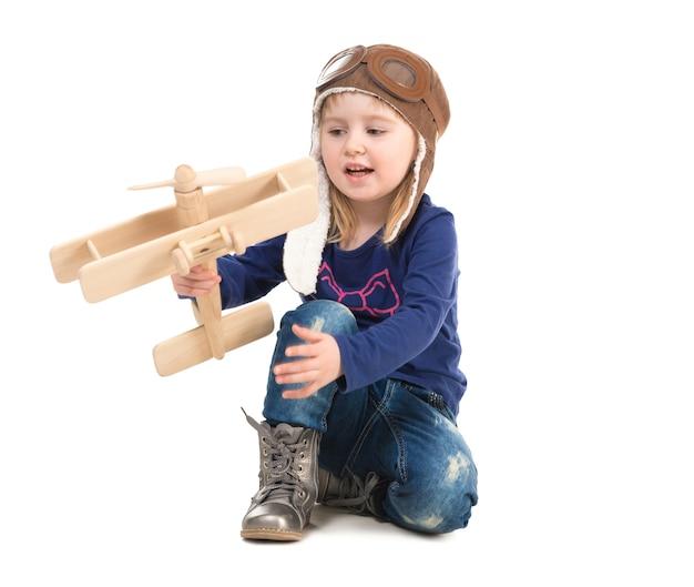 Menina bonitinha no chapéu do piloto com avião de madeira