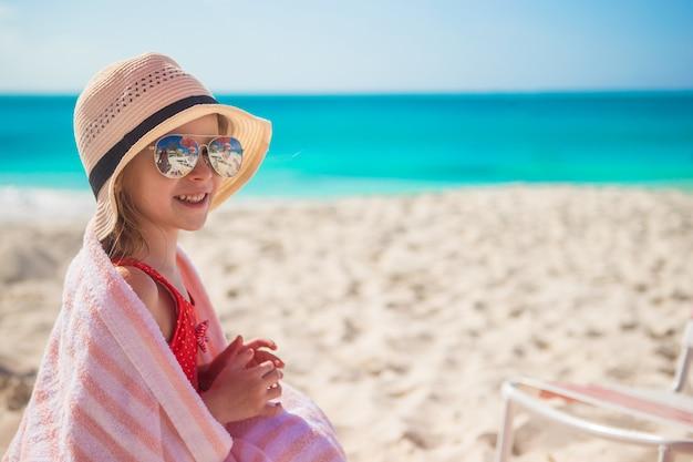 Menina bonitinha no chapéu na praia durante as férias de verão