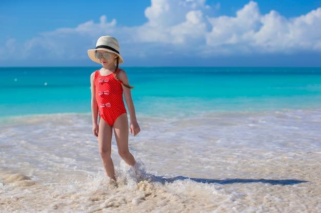 Menina bonitinha no chapéu na praia durante as férias do caribe