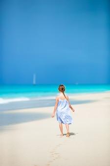 Menina bonitinha no chapéu na praia durante férias nas caraíbas