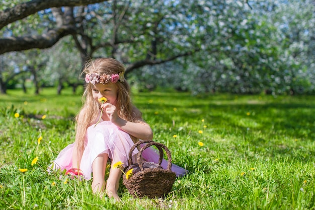 Menina bonitinha no jardim de maçã florescendo no dia ensolarado de primavera