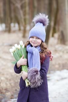 Menina bonitinha no parque com um buquê de tulipas brancas. flores como um presente para o dia das mães das mulheres. 8 de março. páscoa. menina com um buquê para o dia das mães feliz. faz um presente para sua mãe.