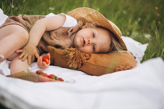 Menina bonitinha no piquenique no parque comendo straberries