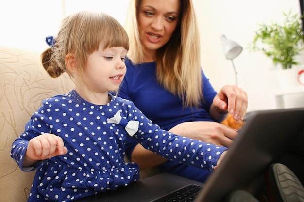 Menina bonitinha no sofá com a mãe usando laptop
