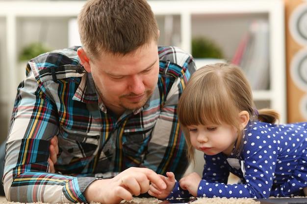 Menina bonitinha no tapete com o pai usando o celular, chamando o retrato da mãe