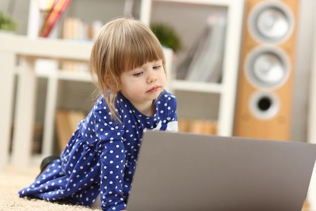 Menina bonitinha no tapete do assoalho usar pc portátil para conversar com o pai dela fora no retrato de negócios. aponte a mão do dedo no conceito de telefonia ip sem fio do crédito de hipoteca bancária de rede web social