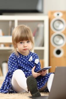 Menina bonitinha no tapete do chão usar celular