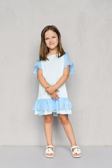 Menina bonitinha no vestido azul e sandálias brancas posando perto da parede cinza