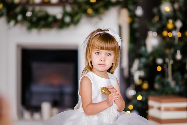 Menina bonitinha no vestido branco com coroa de flores agradável perto da árvore de natal