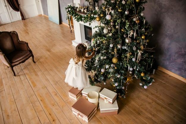 Menina bonitinha no vestido branco com grandes presentes perto da árvore de natal