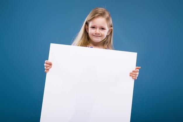 Menina bonitinha no vestido roxo contém cartaz em branco vazio