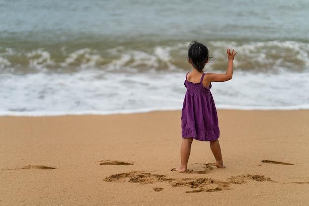 Menina bonitinha no vestido roxo em pé na beira-mar.