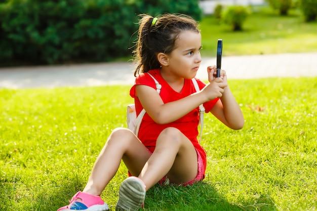 Menina bonitinha olhando a grama através de lupa