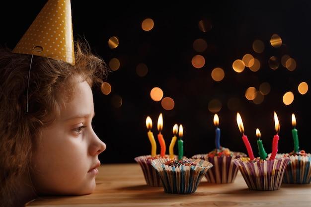 Menina bonitinha olhando as velas em bolos de aniversário.
