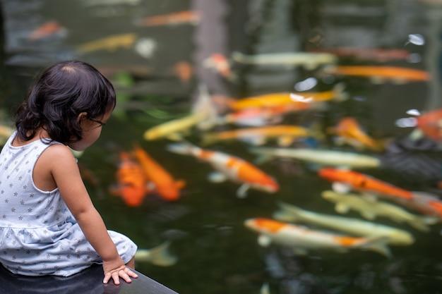 Menina bonitinha olhando peixes carpas koi
