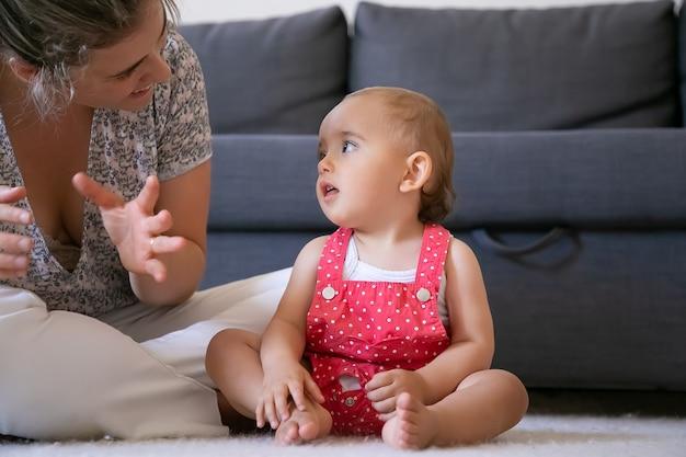 Menina bonitinha ouvindo a mãe com a boca aberta e olhando para ela. mãe recortada sentada de pernas cruzadas no chão e conversando com a filha. adorável bebê sentado com os pés descalços. conceito de fim de semana e maternidade