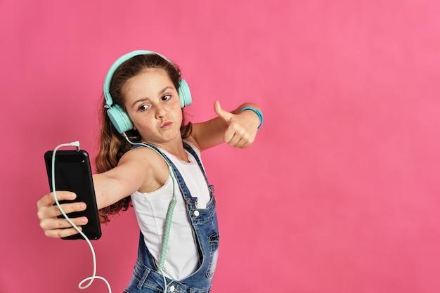 Menina bonitinha ouvindo música com um telefone e fones de ouvido em uma parede rosa