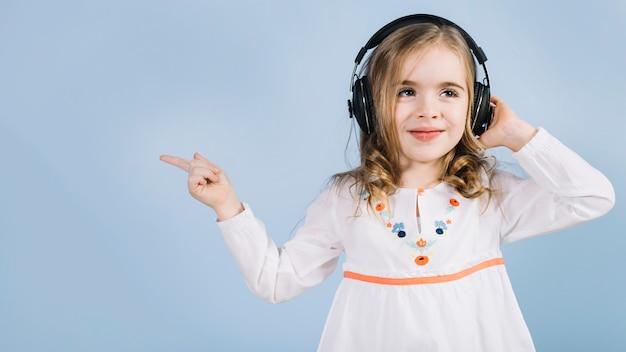 Menina bonitinha ouvindo música no fone de ouvido apontando o dedo para algo