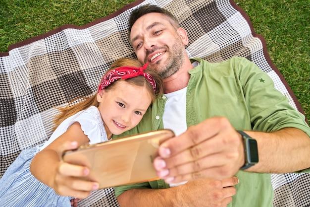 Menina bonitinha passando um tempo com o pai tirando uma selfie usando o smartphone enquanto está deitada em um