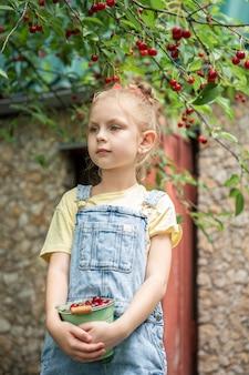 Menina bonitinha pegando uma cereja em uma árvore no jardim de cerejeiras